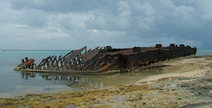 The remains of Blacktip Island's supply barge rests on shore of the Caribbean island.
